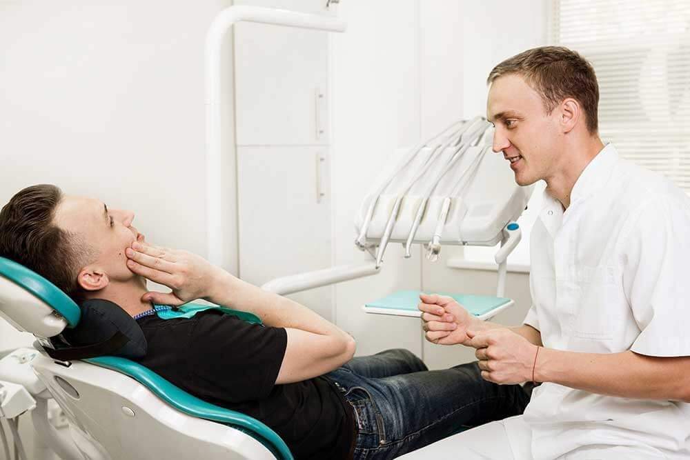 patient laying in dental chair talking to medical professional while gripping jaw