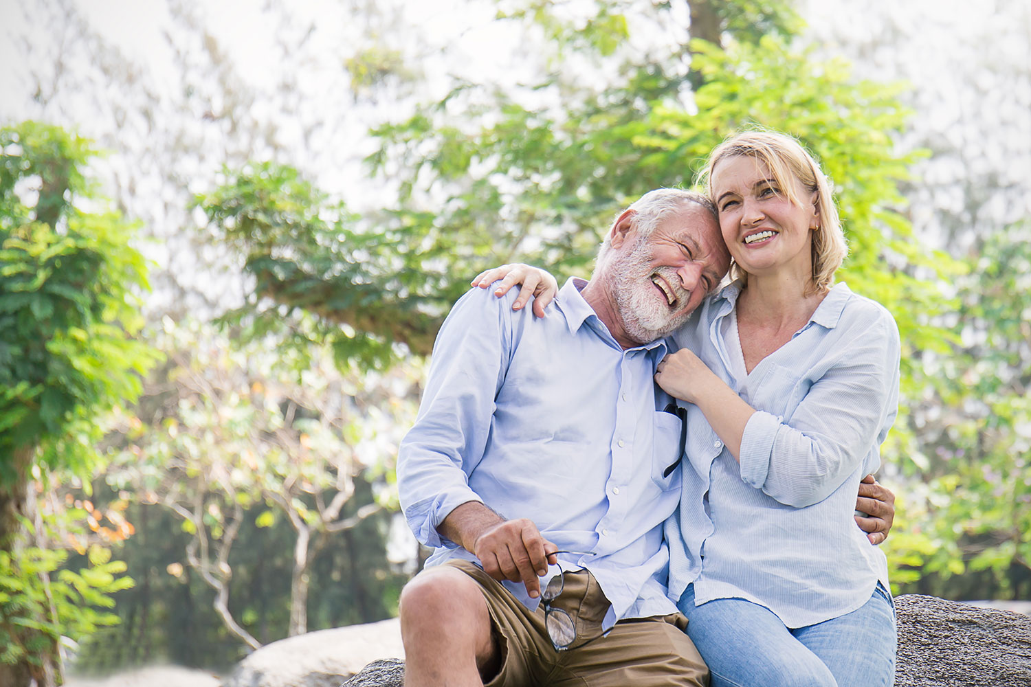 older couple hugging and smiling in front of trees